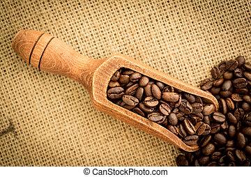 Wooden shovel full of coffee beans on burlap sack