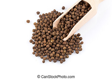 Wooden shovel with large black peppercorn scattered from it