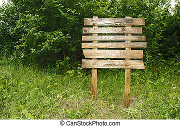Wooden sign on a green grass lawn