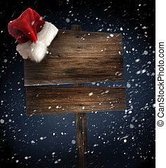 Wooden sign with santa hat on snowy background - Weathered...