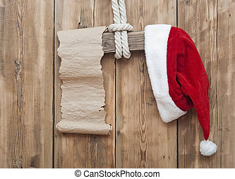 wooden sign with Santa's hat and blank paper scroll on a wooden background