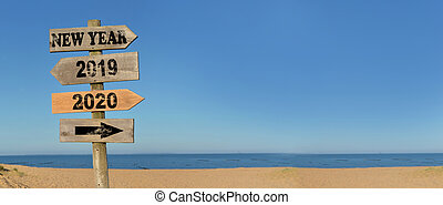 wooden signpost happy new year on the beach with opposed arrows 2020 and 2019