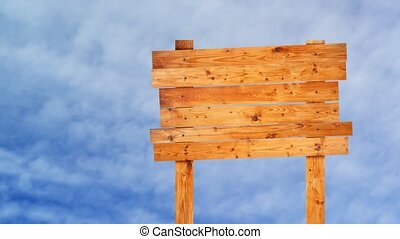 Wooden signpost over white clouds t