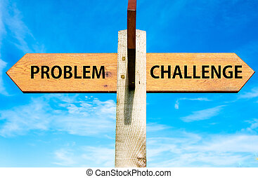 Wooden signpost with two opposite arrows over clear blue sky, Problem versus Challenge messages, Problems solving conceptual image