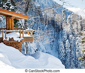 Wooden ski chalet in snow, mountain view