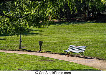 Wooden slatted bench in a verdant green park with neat lawns and woodland trees at the side of a walkway or path