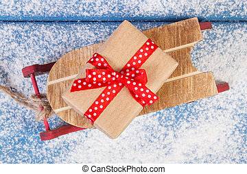 Wooden sled and wrapped gift with ribbons for Christmas or...