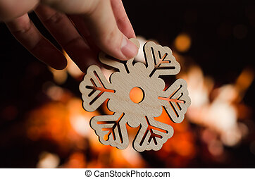 Wooden snowflake christmas decoration on fireplace background