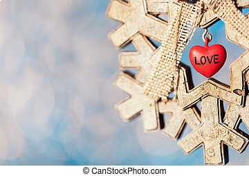 Wooden snowflake Christmas decoration with small red heart on sparkling bokeh background, shallow depth of field