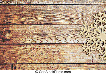 Wooden snowflake on a weathered wood background