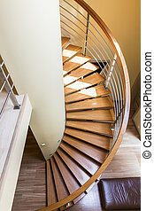 Wooden spiral staircase with minimalist railing in bright...