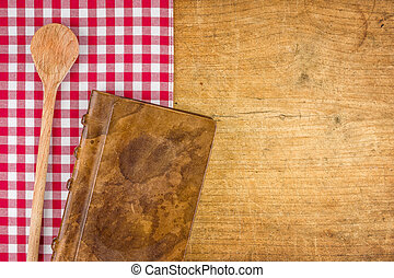 Wooden spoon and book on a wooden board with a checkered tablecloth