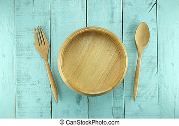 Wooden spoon and fork placed near bowl on a green wood background.