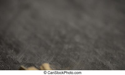 Wooden spoon and garlic over black chalkboard background.