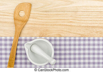 Wooden spoon and mortar on a purple checkered table cloth on a wooden background