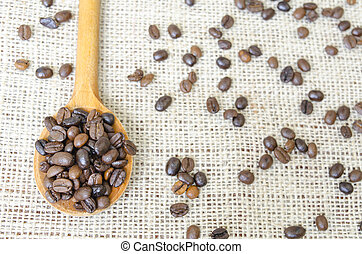 Wooden spoon full with roasted coffee beans