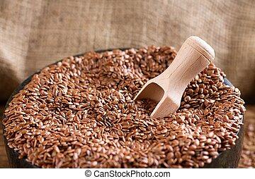 Wooden spoon inside heap of flax seeds