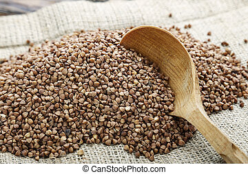Wooden spoon of roasted buckwheat. gluten free ancient grain for healthy diet