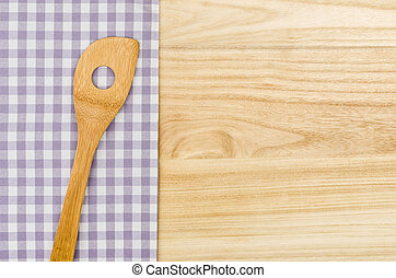 Wooden spoon on a purple checkered table cloth on a wooden background