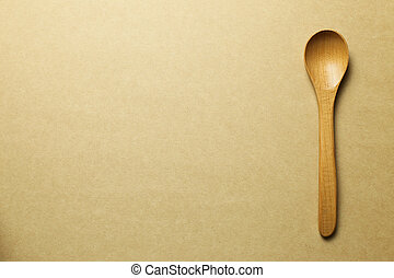 Wooden spoon on brown background