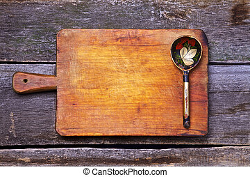 Wooden spoon on old chopping board