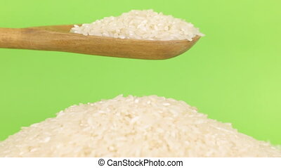 Wooden spoon pours grains rice at heap of rice on a green screen.