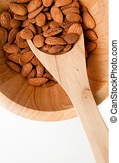 Wooden spoon with almonds in in a bowl