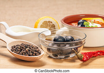 Wooden spoon with black peppercorn, bowl with olives, dried red pepper on cutting board and ceramic soup bowl with saltwort, sauceboat and cut lemon.