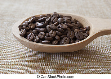 Wooden spoon with coffee beans on sackcloth.