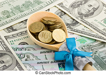 Wooden spoon with coins on a background of money
