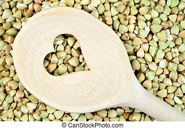 Wooden spoon with heart shape in a green buckwheat