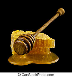 Wooden spoon with honey isolated on black background