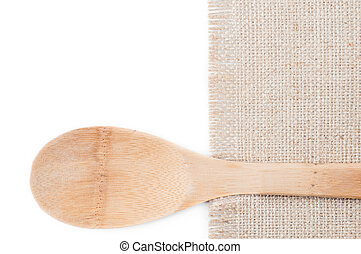 Wooden spoon with piece of burlap on a white background