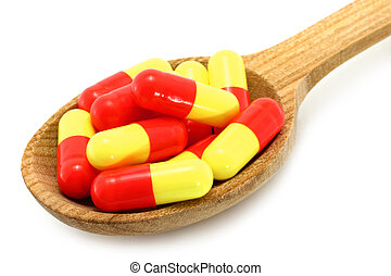 Wooden spoon with pills on a white background