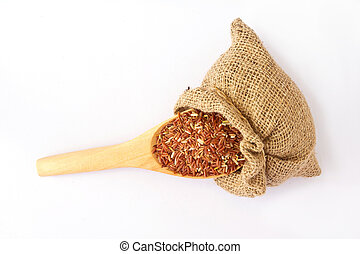 Wooden spoon with red rice in canvas sack.