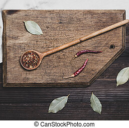 wooden spoon with spices on a cutting board