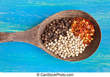 Wooden spoon with three type of black, white and chili pepper, on blue wooden background, top view