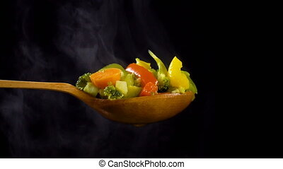 Wooden spoon with vegetables and steam on black background