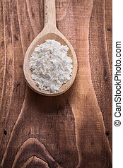 wooden spoon with white natural flour on vintage board food and