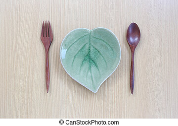 Wooden spoon,fork and dish in top view on wood background.