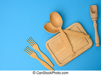 wooden spoons, forks and rectangular cutting board on a blue background
