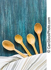 Wooden spoons on a blue vintage wooden background. Flat lay, top view, copy space.