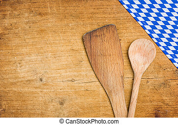 Wooden spoons with a bavarian tablecloth on a wooden background