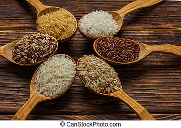 Wooden spoons with different rice types on the wooden background