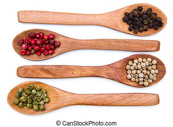 Wooden spoons with mixed peppers on a white background seen from above