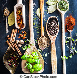 wooden spoons with spices and herbs on textured black...