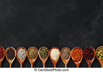 Wooden spoons with various spices on black background