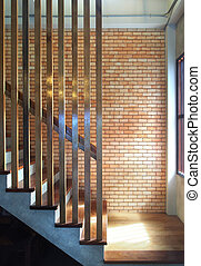 Wooden staircase with red brick wall background.