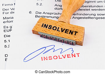 a stamp made of wood lying on a document. inscription insolvent