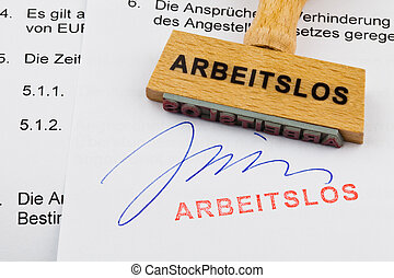 wooden stamp on the document: unemployed - a stamp made of...